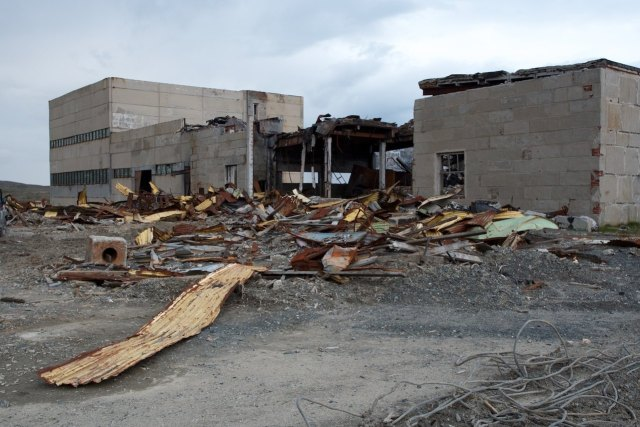 Damaged physical structure, surrounding area in disarray, abandoned