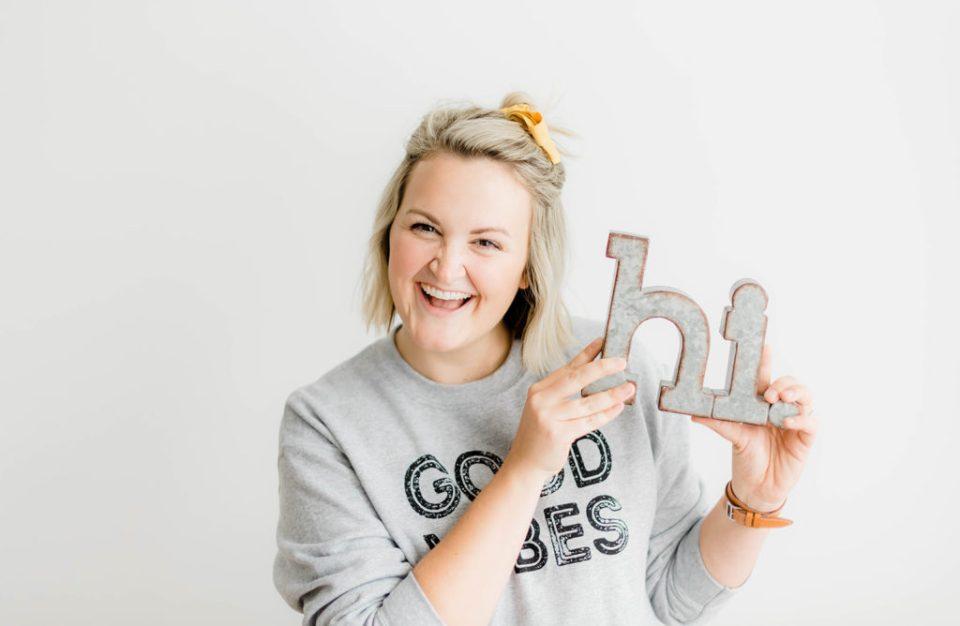 woman wearing good vibes sweatshirt holding metal hi sign