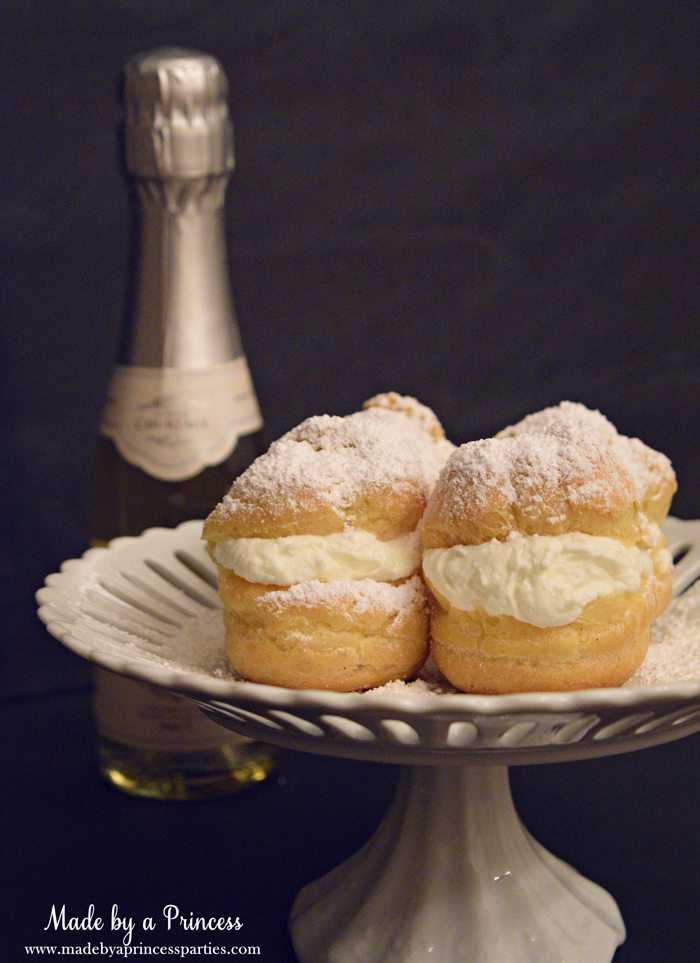 easy-champagne-cream-puffs-recipe-with-powdered-sugar-on-a-cake-stand-and-champange-on-the-side
