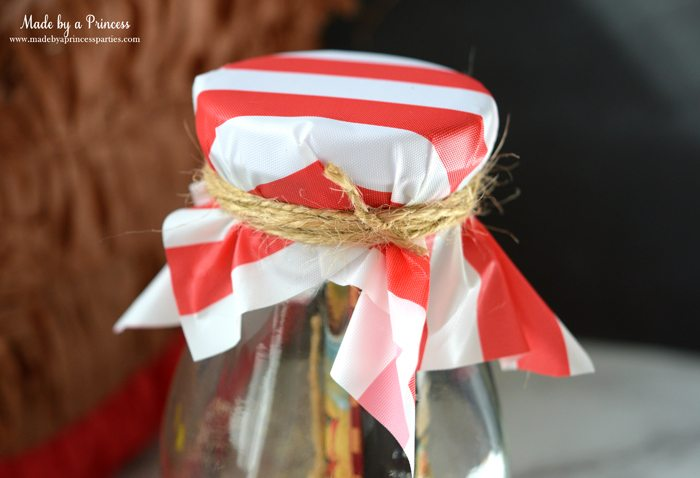 Pirate Bottle Invitations Party Idea place piece of plastic tablecloth on glass milk bottle and wrap twine around