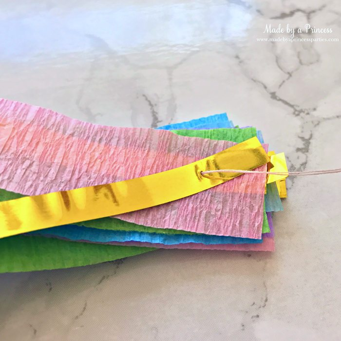unicorn princess party hat idea tutorial layer crepe paper and gold fringe bring threaded needle through all layers