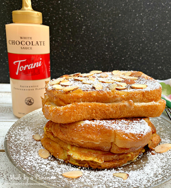 Garnish marzipan stuffed french toast with toasted almonds. powdered sugar and Torani White Chocolate Sauce