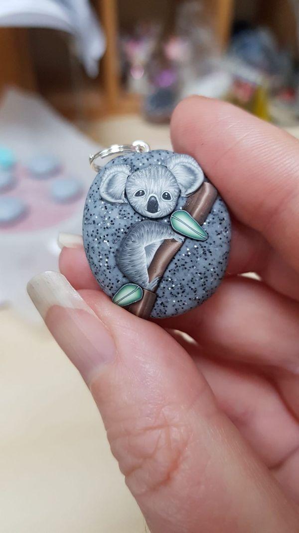 clay charm showing koala on granite pebble held between thumb and figure
