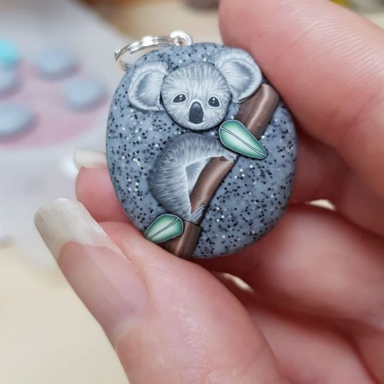 clay charm showing koala on granite pebble held between thumb and figure