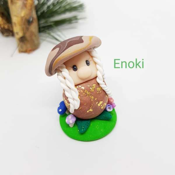 small beige gnome clay ornament resembling a mushroom mounted on green base in centre with background foilage top left