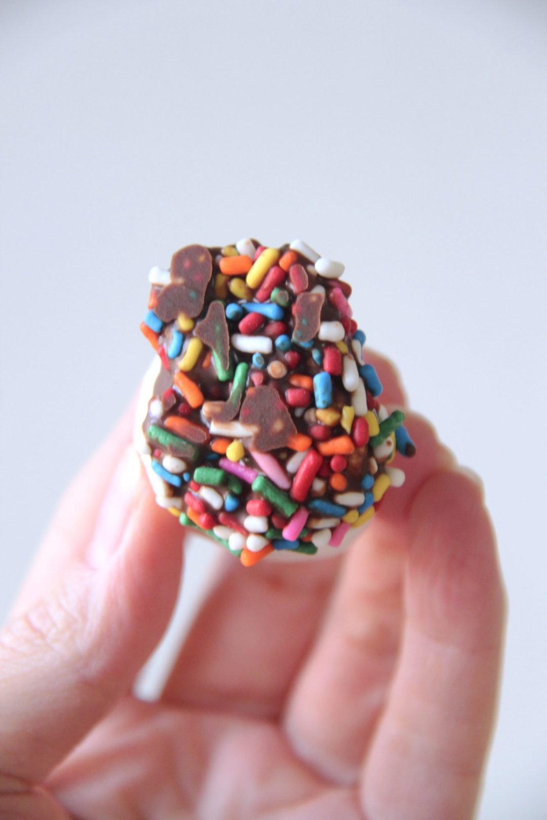 Want a kid-approved treat that's as easy as it is delicious? Try your hand at chocolate covered marshmallows with rainbow sprinkles. | madewithlev.com #cookingwithkids #desserts #sweettreats #chocolate #marshmallows #dessertrecipes #easydesserts