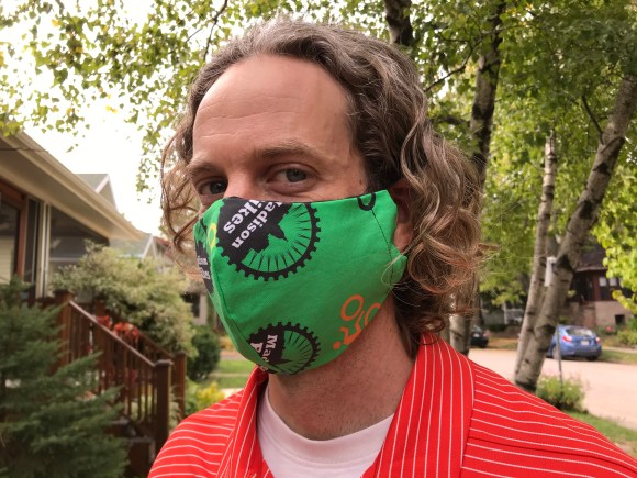 A man wearing a green face mask with the Madison Bikes logo on it