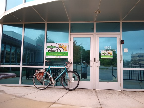 A bicycle leaning on a glass facade, with Madison Bike Week posters attached to glass