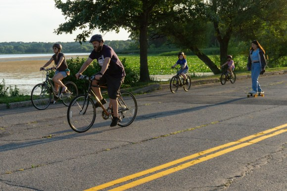 Two adults and two children riding bicycles and one female teenage riding a skateboard on Vilas Park Drive