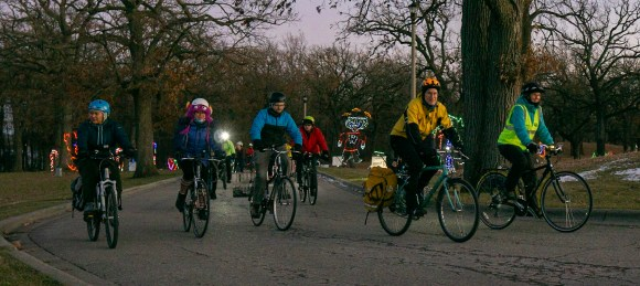 A group of people biking through the Holiday Fantasy in Lights course at Olin Park