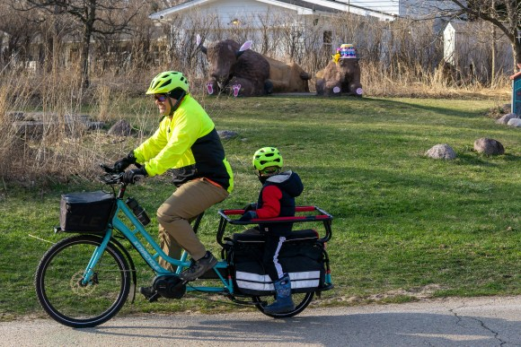 Two differently-sized people riding a bike together along the SW commuter path