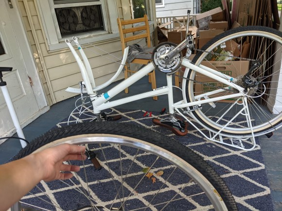 Bike on a porch with front wheel removed. A hand in the foreground holds a wheel in front of the bike.