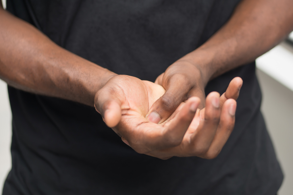 Man with hand pain caused by diabetes