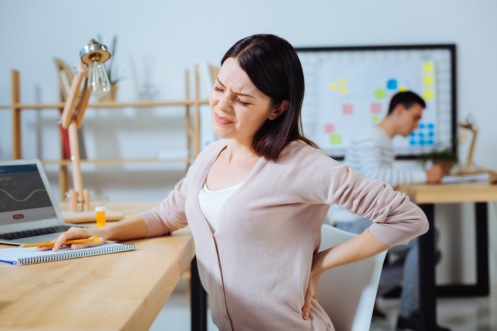 Women sitting at a table holding back in pain