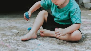 child in green shirt and black shorts sitting on ground Disciplina Positiva