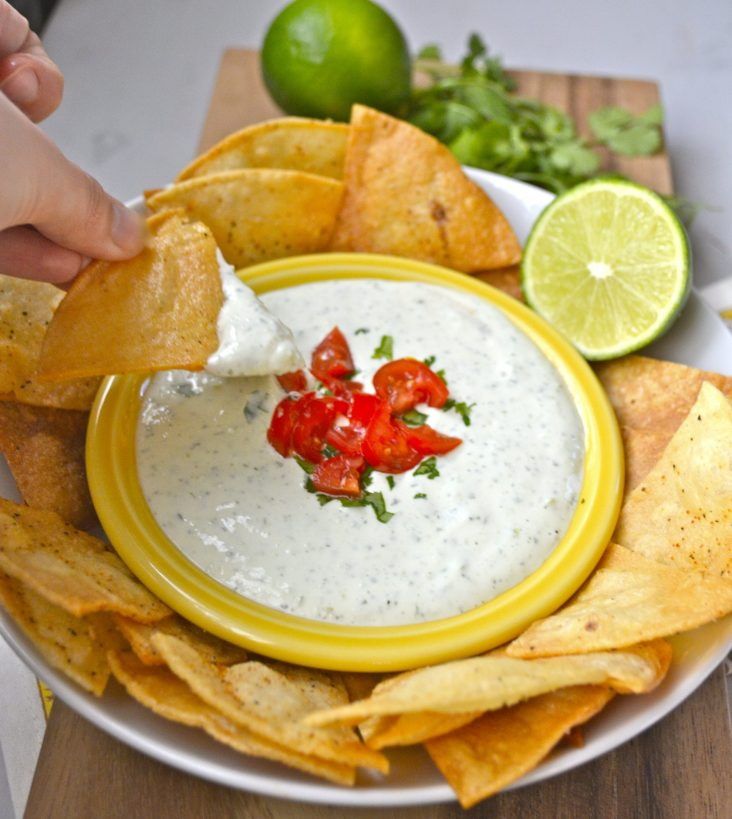 a tortilla chip being dipped into a bowl of Jalapeno Ranch Dip