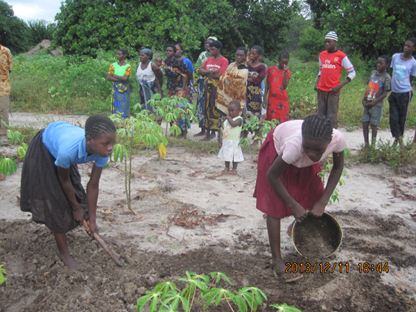 Women from the community learn how to weed at demo farm.