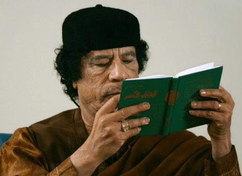 """Guide Mouammar Kadhafi avec le Livre Vert: héros africain toujours populaire dans des pays africains et la diaspora. Il disait """"l'Afrique, c'est mon pays""""."""