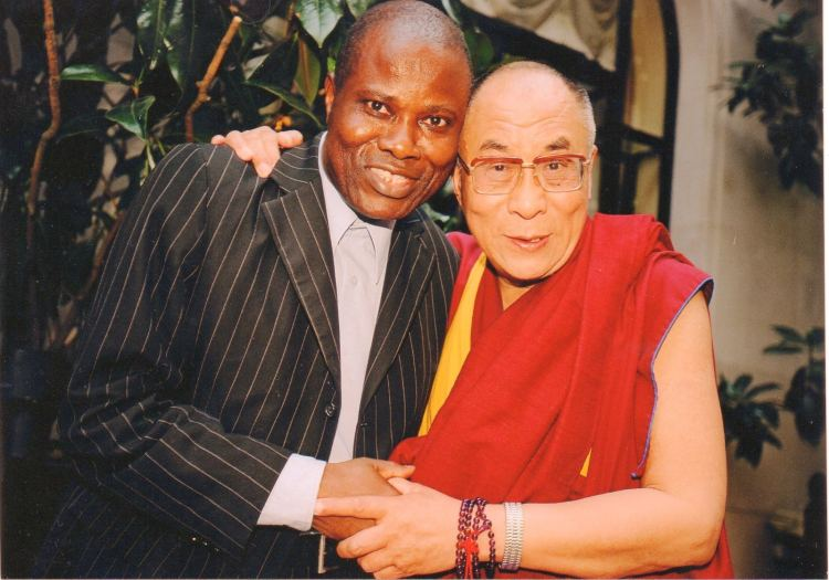 «J'ai pu initier cette conférence de presse de Sa Sainteté le Dalaï-Lama grâce aux fondamentaux appris à l'Isti. Il y avait 927 journalistes du monde à notre conférence de presse à l'hôtel George V à Paris (octobre 2003). Le Dalaï-Lama me disait de rester moi-même, spirituellement et comme journaliste congolais. Et il m'embrassa pendant 13 minutes pour cette conférence devant les caméras». Photo Lilo Miango et Dalaï-Lama lors de cette conférence de presse: photographe Suisse Manuel Bauer (Lookat Photos Zürich/Suisse).