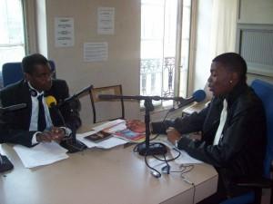 """Le journaliste Nzunga Mbadi (lunettes) recevant un invité lors de son émission légendaire """"Tam-Tam Magazine""""(Paris)"""
