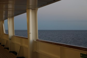 View off the starboard side, toward the bow. Promenade Deck. At sunset.