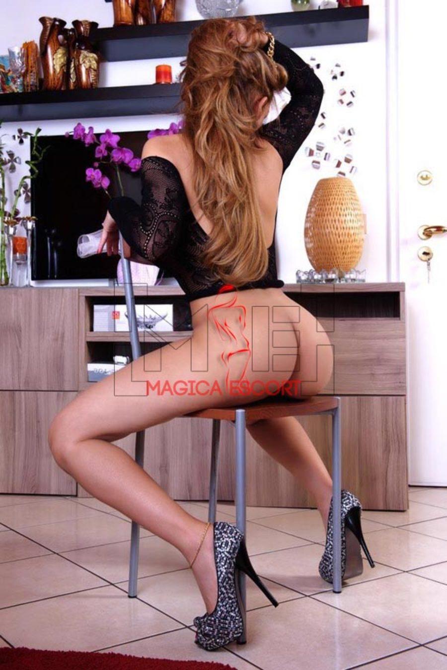 Karla escort Piacenza è nuda in una posa molto erotica sulla sedia di casa.