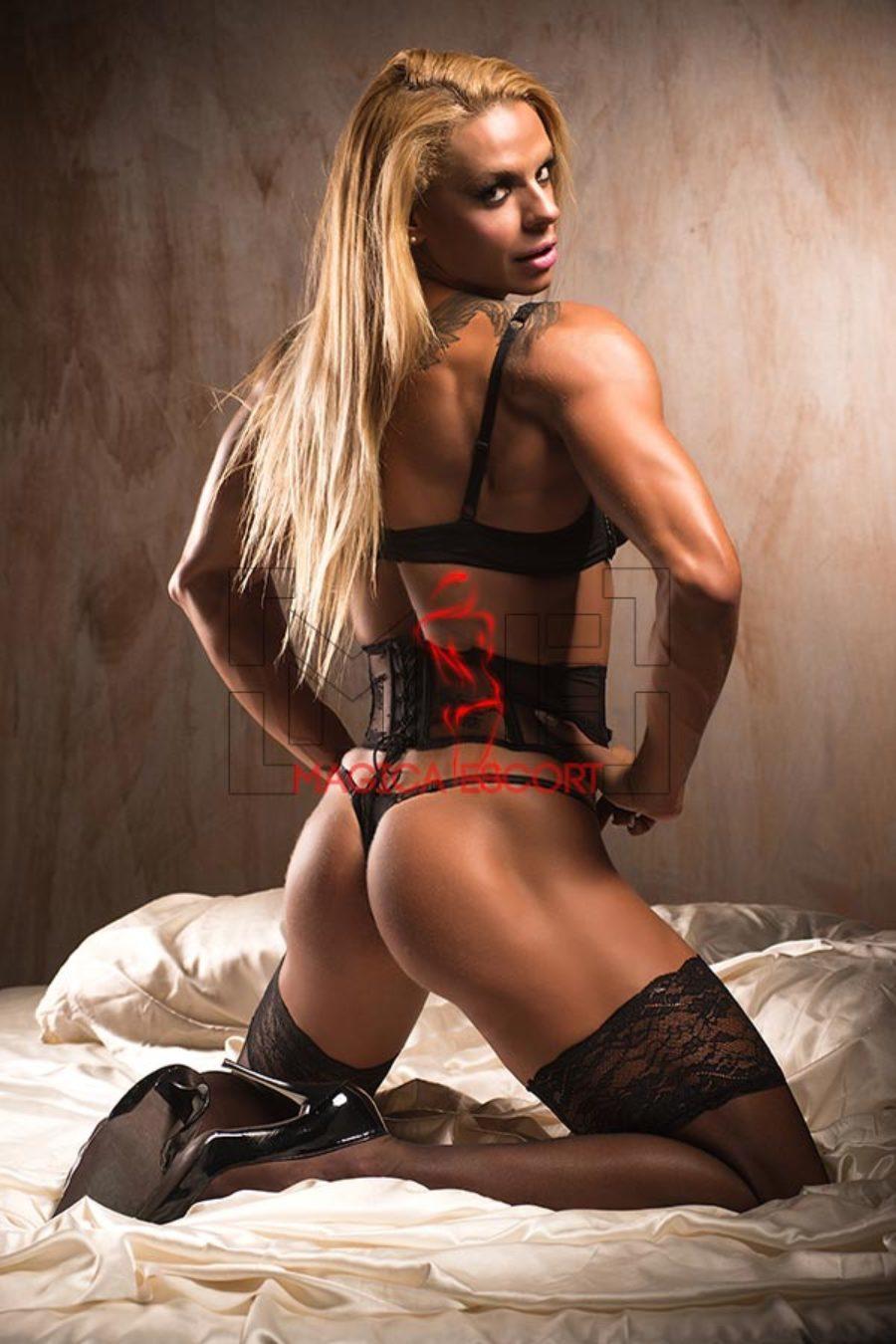 Larissa escort Roma in ginocchio sul suo letto.