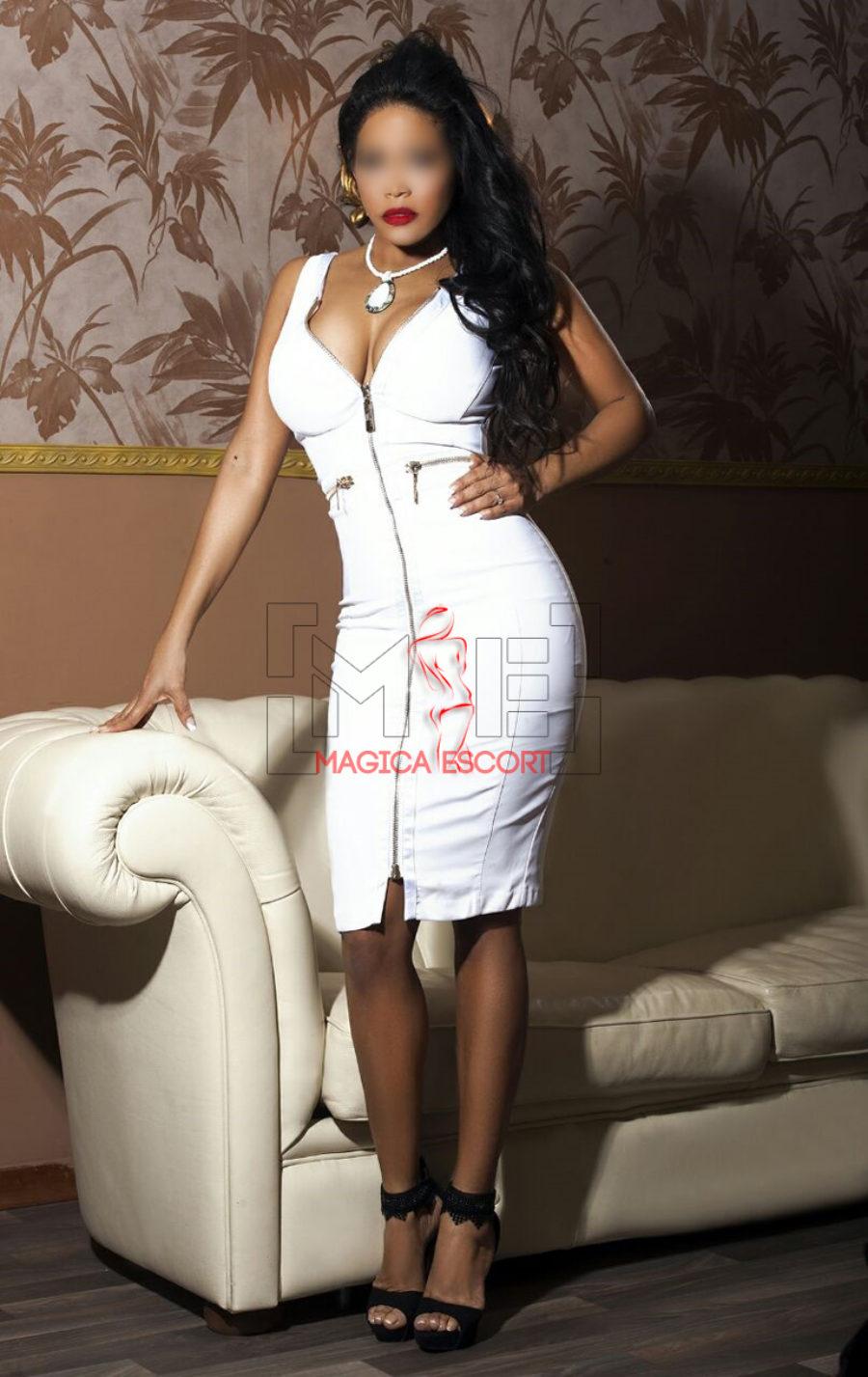 Linda escort Brescia mostra una scollatura profonda indossando questo abito bianco.