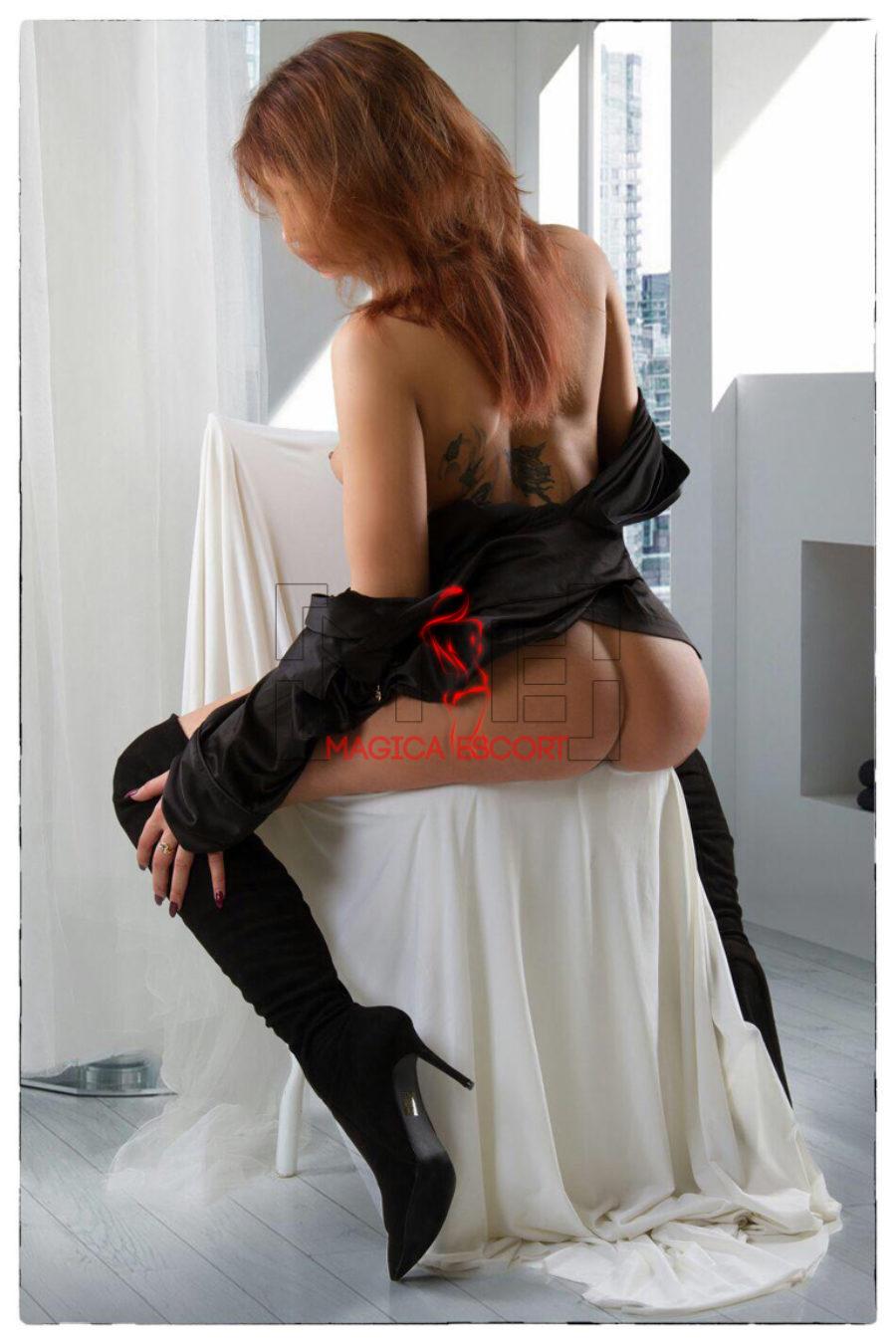 Emeshe escort high class è seduta in una sedia senza indossare le mutandine.