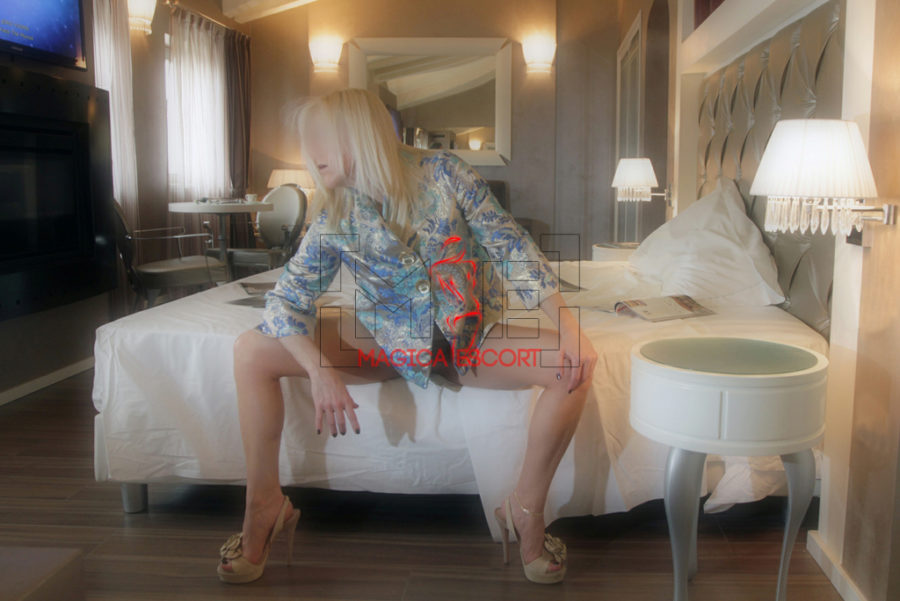 Lea escort Monza seduta nel letto di una camera d'albergo con una camicetta floreale ed i tacchi alti.