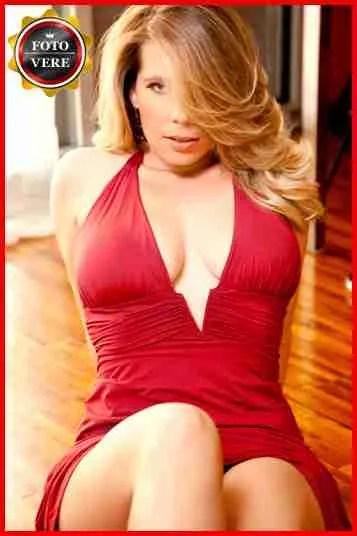 Giselle top class escort Torino con un abito rosso fuoco e lo sguardo provocante.