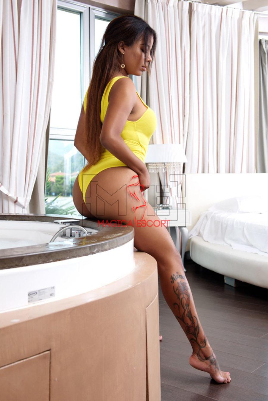 Anais escort venezuelana indossa un costume giallo nella sua camera da letto.