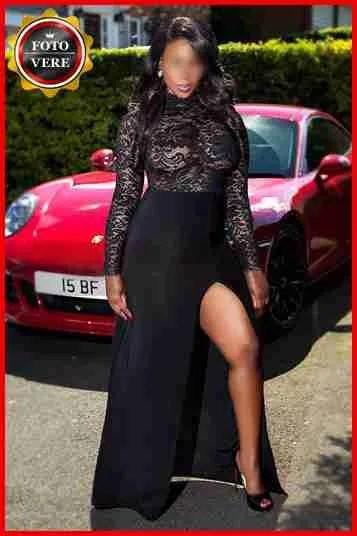 Ashley top class escort Milano indossa un abito da sera con uno spacco profondo. Magica Escort.