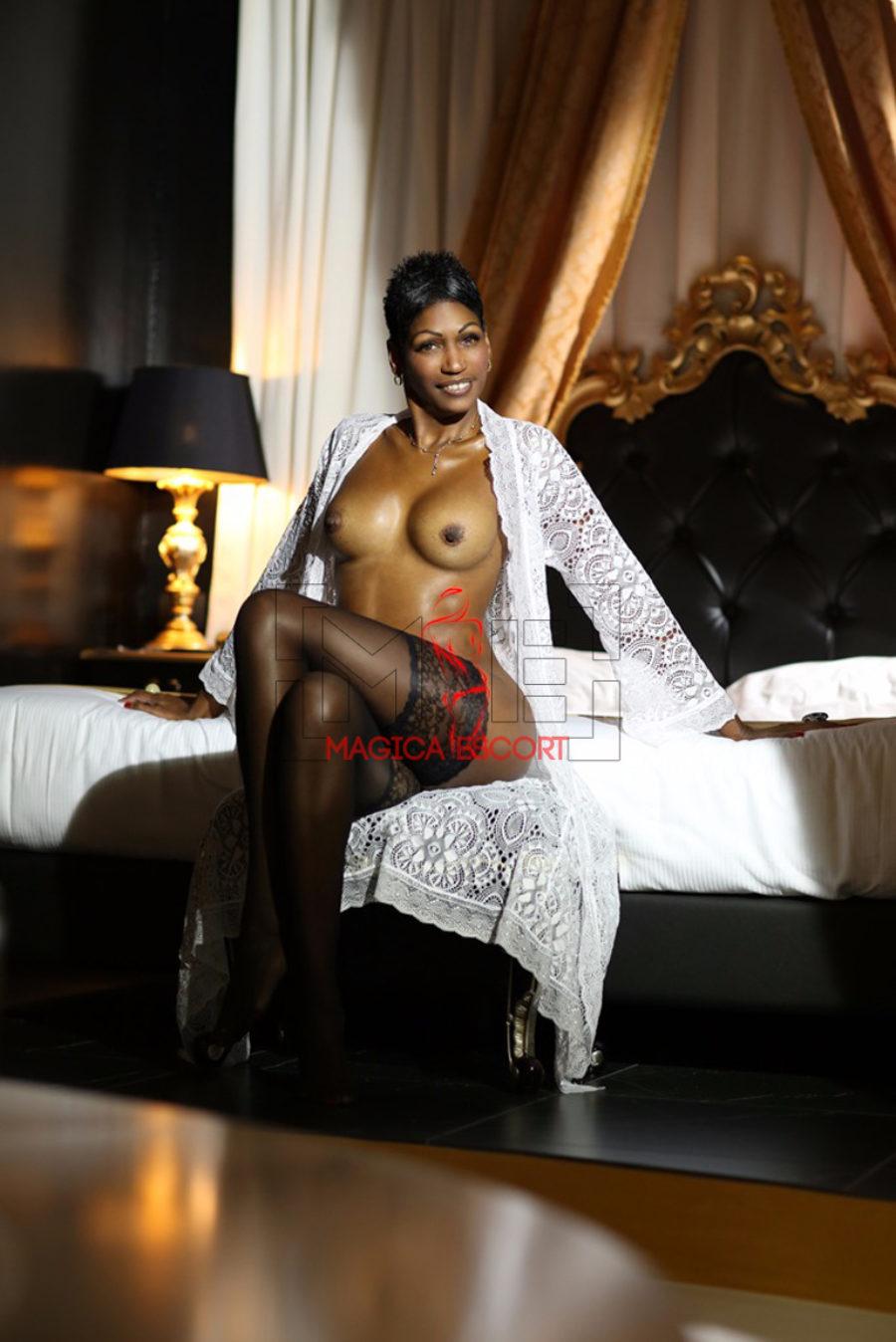 Escort cubana Sharon a seno nudo e con le autoreggenti seduta nel suo letto. Magica Escort.