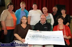 Seán Prendergast receiving a cheque on behalf of the Kerry - Cork Health Link Bus from the proceeds of the 2014 Carmel Linehan memorial Run / Walk committee at Knocknagoshel Community Centre. Making the presentation are: Bridget Scanlon (left) and Catherine Brosnan. Back from left: Catherine Brosnan, Mary McAuliffe, Catherine Browne, Eileen O'Connor, Nelius Linehan and Marie O'Callaghan. ©Photograph: john Reidy