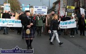Marching to a different tune: Linda Casey from Abbeyfeale goes about her Saturday afternoon shopping as Piper, Denis O'Reilly leads the Right2Water protest march in Castleisland today. ©Photograph: john Reidy
