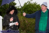 Nancy Foran reading the roll of honour as John Breen provides shelter during Friday evening's commemoration to the memory of Jack Flynn, Jack Prendiville and Richard Shanahan at Castle View, Castleisland. ©Photograph: John Reidy 1-5-2015