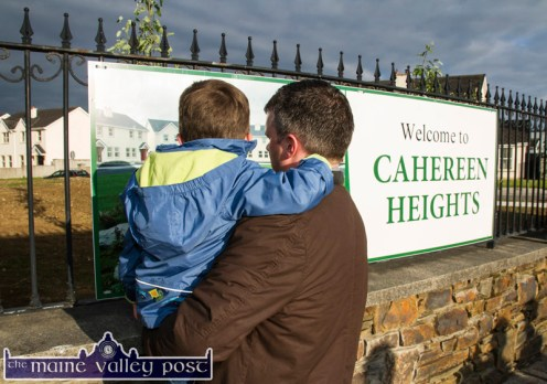 Here's to the future: Residents, Eamonn Moriarty and his little boy, Billy admiring the new entrance signage at Cahereen Heights as the renewal works near completion on Thursday evening. ©Photograph: John Reidy