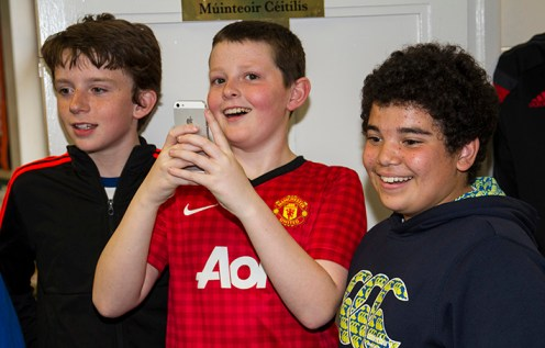 Luke's brother, Alex (centre) recording the event with class-mates, Caoimhín de Barra, (left) and Yousif Breathnach looking on and recording Luke and Conor's charitable act during the Shave or Dye fundraiser at Gaelscoil Aogáin on Friday. ©Photograph: John Reidy