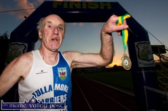 Tullamore Harriers athlete and Over 70s winner, Jim Langan, complete with training run injuries, holding his three x 5K medal aloft after he completed the September 2016 series of 5K road races at An Ríocht AC. ©Photograph: John Reidy
