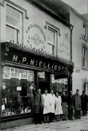 A photo of McElligott's Business and staff circa 1930's. (L-R) Paddy McElligott, Nora O'Connor(nee Brosnan, Josie Thompson, Feales Bridge; Eily Burke nee O'Leary - Burkes Garage; Sheila Cournane, nee Drum; Tom Broderick and Jerry Kelliher. Courtesy of Gina McElligott.