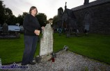 Bridie O'Connor-Begley sprinkling holy water on the grave of her ancestors during the Ecumenical Service and Blessing of Graves at St. Stephen's Churchyard on Tuesday evening. ©Photograph: John Reidy
