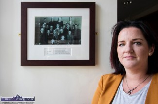Links run deep: Local woman, Cecily O'Connor pictured at Castleisland Garda Station beside a photograph from 1951 which includes her grandfather and Co Kildare native, Garda Mick Behan. Ms. O'Connor was attending the tribute to the late Detective Garda Colm Horkan. ©Photograph: john Reidy