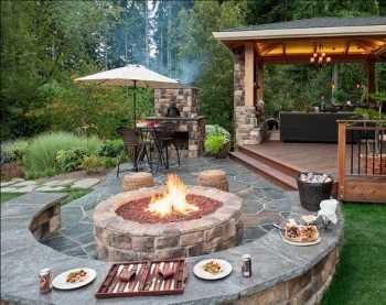 Backyard fire pit, stone seat wall, Frisco TX backyard, natural stone outdoor living area.