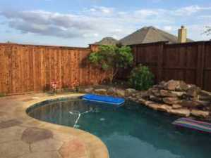 Backyard Pool Project Before Professional Landscaping in Prosper Texas backyard home. The new landscape design plans include replacing old mulch in bed areas with river rocks and old plants with new tropical landscape.
