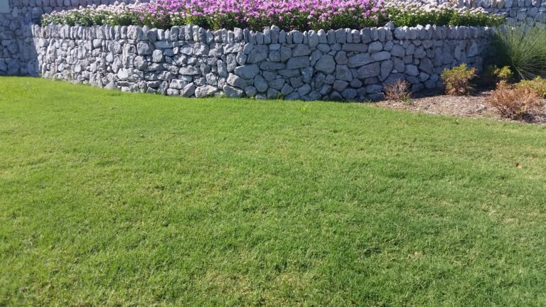 Dry stacked stone wall garden bed borders