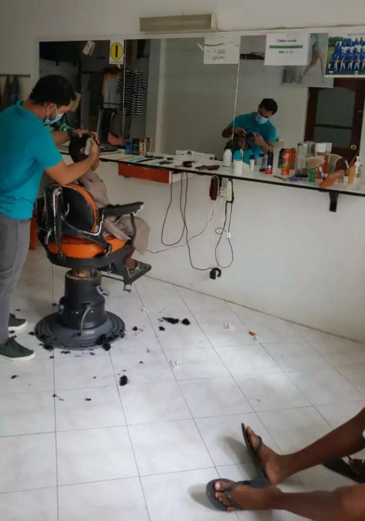 barbearia manu at work in his barbershop in vila do maio