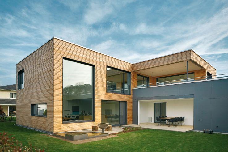 Une des fenêtres du séjour, dont la hauteur correspond aux deux étages, laisse entrer la lumière librement.