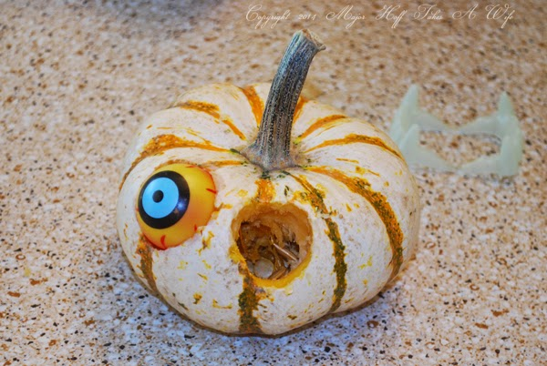 Placing plastic eyes into pumpkin for head