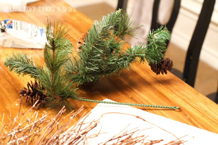 Bend the greenery to make it a better fit on the wreath. World Market inspired wreath. A fun twist on a Christmas wreath. Make a winter wreath that will last all season long and well past. This cute grapevine wreath is adorned with a tiny bird, pinecones, greenery and pom poms. You won't believe how cheap and easy this was to make! And so simple! #Christmas #winter #holiday #wreath #nature #knockoff